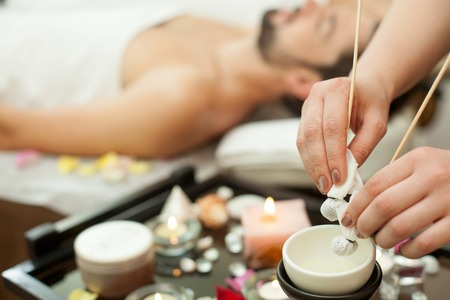 Closeup of hands of a masseur. Young man being massaged with an herbal compress. The masseuse is preparing massage sticks Stock Photo
