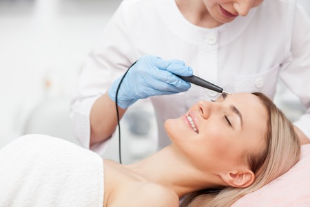 fractional: Cheerful young girl is getting facial treatment by beautician. She is smiling. The lady is lying with relaxation