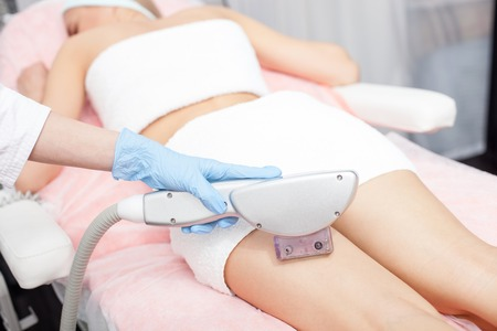 fractional: Close up of hand of professional beautician undergoing laser skin treatment on human legs. The woman is lying with relaxation. The cosmetologist is wearing a glove