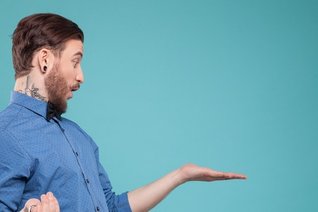 Handsome young bearded hipster is showing something with surprise. He is standing and raising arm sideways. Isolated and copy space in right side 스톡 콘텐츠
