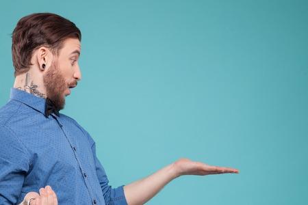 Bel giovane pantaloni a vita bassa con la barba sta mostrando qualcosa con la sorpresa. Egli è in piedi e alzando il braccio di lato. Isolata e copia spazio nel lato destro Archivio Fotografico - 49993309