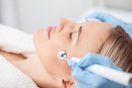 fractional: Beautiful young woman is getting cavitation treatment at spa. She closed her eyes with enjoyment. The beautician is touching equipment to her face