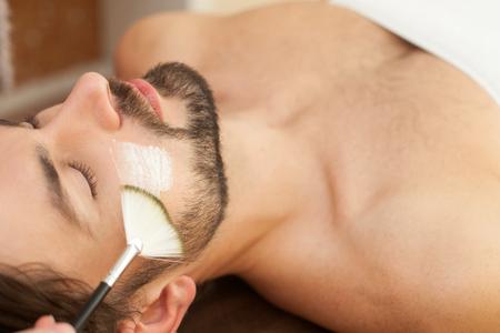 男性の顔をブラシにクリームを適用する美容師の手のクローズ アップ。男が横になっているとスパでリラックス 写真素材