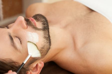 Close up of hand of beautician applying cream on male face with a brush. The man is lying and relaxing at spa