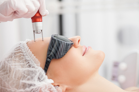 Close up of hands of professional beautician making skin treatment for woman. The lady is smiling with relaxation. She is lying and wearing goggles 스톡 콘텐츠