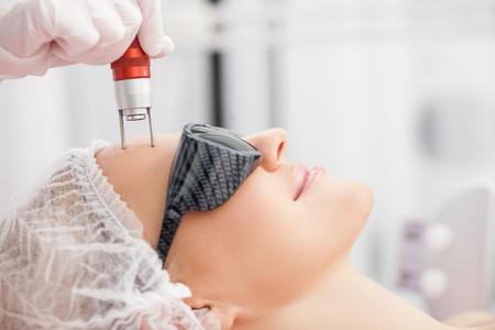 Close-up van handen van professionele schoonheidsspecialiste huid behandeling voor de vrouw. De dame lacht met ontspanning. Ze ligt en het dragen van een bril
