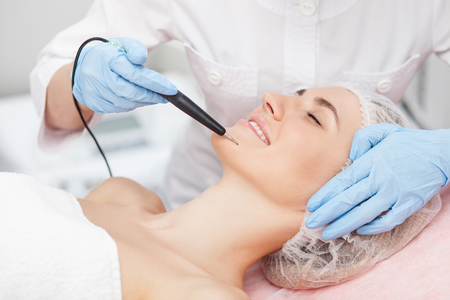 Close up of hands of professional cosmetologist treating human skin with laser. She is touching the equipment to the face. The woman is lying and smiling