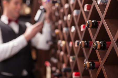 sommelier: Cheerful young sommelier is choosing wine in cellar. He is smiling. Focus on bottles in shelf Stock Photo
