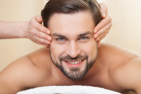 매력적인 남자 스파에서 머리 마사지를 받고있다. 그는 거짓말을하고 웃고있다. 남자는 만족을 기대하고있다. 여성 손은 그의 사원을 마사지하고 있습