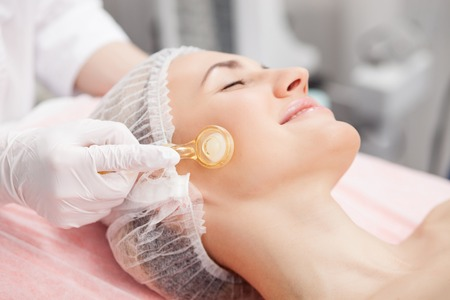resurfacing: Beautiful woman is getting skin treatment at spa. The beautician is touching a roller to her skin. The woman is lying and smiling Stock Photo