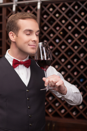 wine glasses: This wine smells well. Cheerful young sommelier is examining the quality of wine. He is standing with closed eyes. The man is smiling with pleasure Stock Photo