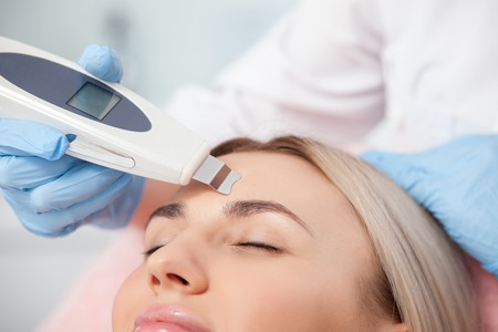 resurfacing: Close up of hands of cosmetologist undergoing skin treatment with the equipment. The young woman closed her eyes with pleasure Stock Photo