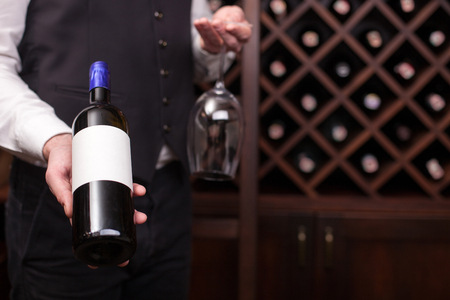 Close up of hands of young sommelier presenting a bottle of red wine. He is standing in cellar and holding a glass. Copy space in right side