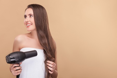drying: Cute young woman is drying her long wavy hair. She is standing and holding a hairdryer. The lady is smiling and looking aside happily. Isolated and copy space in right side Stock Photo