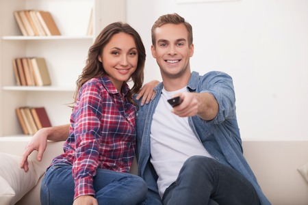 they are watching: Beautiful young married couple is watching tv with joy. They are sitting on sofa and embracing. The man is holding the remote. They are smiling