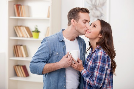 young couple hugging kissing: Cute loving couple is standing and embracing. They are holding a cup of coffee and smiling. The man is kissing a woman with love