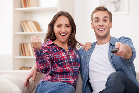 they are watching: Attractive young husband and wife are watching television together. They are sitting on sofa and embracing. The man is holding a remote. The woman is gesturing happily and smiling