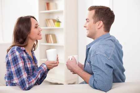 hot boy: Cheerful young married couple is drinking tea and smiling. They are sitting on sofa and talking