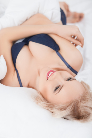 expressing: Attractive blond girl is underwear is expressing her sexuality. She is lying in bed and wearing a blanket.