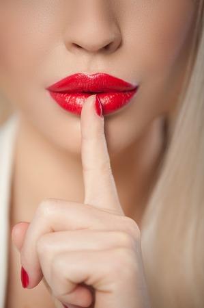 silencio: Primer plano de los labios rojos de chica seductora levantan el dedo a la boca