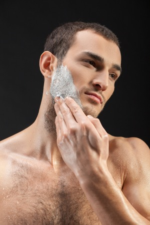 hairy: Waist up portrait of attractive young man shaving his beard. He is standing and applying shaving foam on his chin.