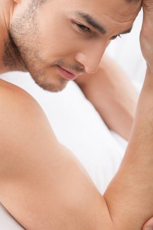 sexualidad: Hombre joven atractivo que est� evidenciando su sexualidad. Que se ha quedado en la cama y mirando hacia adelante con la pasi�n