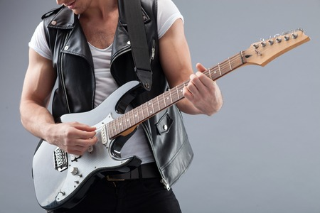 Professional rock musician is creating wonderful music with a guitar. He is standing and playing with joy. Stock Photo