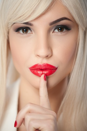 secretly: Close up portrait of beautiful young blonde woman raising her finger to red lips secretly