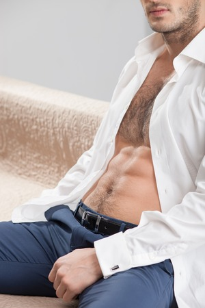 sexualidad: Hombre alegre que est� expresando su sexualidad. �l est� sentado en el sof� con la relajaci�n.