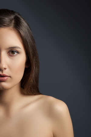 image style: Waist up portrait of half face of beautiful young woman caring of her skin. She is standing with shoulders and looking at camera with temptation. Isolated on black background Stock Photo