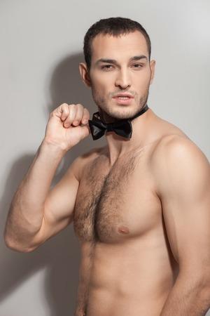 sexualidad: Retrato de separador alegre expresar su sexualidad. Él está de pie y tocar su pajarita.
