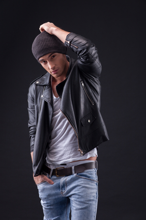 image style: Portrait of cheerful biker standing in a leather jacket. He is touching his hat and keeping hand in a pocket. The man is looking forward with desire. Isolated