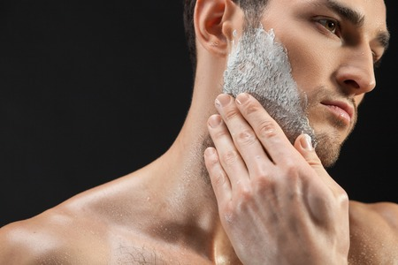 hairy: Portrait of cheerful young man applying shaving foam on his face.