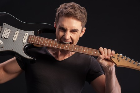 rock guitarist: Waist up portrait of crazy rock guitarist biting the electric guitar with efforts. He is standing and looking at camera with aggression. Isolated