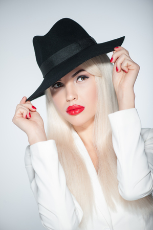 secretly: Waist up portrait of young woman with black hat and white wig. She is standing and staring at camera secretly. Isolated Stock Photo