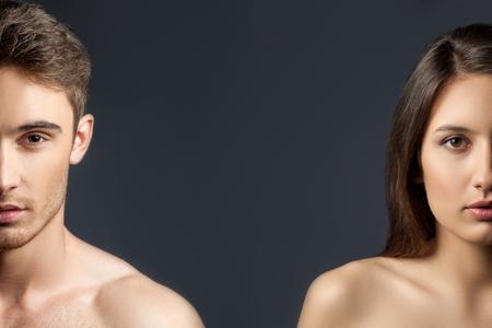 魅力的な若い男性と女性の完璧なボディと滑らかな肌の半分の顔の肖像画。黒の背景に分離