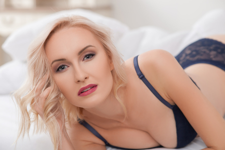 temptation: blond girl is expressing temptation. She is lying in bed and wearing blue underwear.