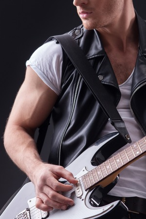 seriousness: Skillful guitarist is playing the guitar with inspiration. He is standing with seriousness. Isolated