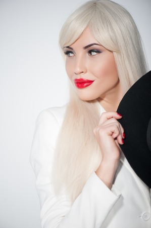 secretly: Portrait of young woman masking her appearance with black hat and white wig. She is standing and looking aside secretly. Stock Photo