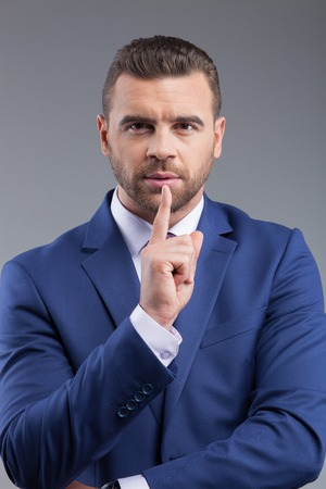 seriousness skill: Waist up portrait of successful young business worker is asking for silence. He is standing and looking at camera with seriousness. The man is raising finger to his mouth. Isolated on grey background Stock Photo