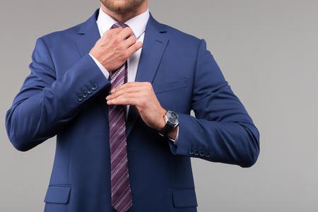 joven y exitoso hombre de negocios está preparando para la reunión. Él está de pie y ajustando la corbata. Aislado en el fondo gris