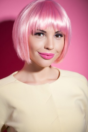 image style: Portrait of cute coquette standing and smiling. The woman is flirting and looking forward playfully. She is wearing pink wig. Stock Photo