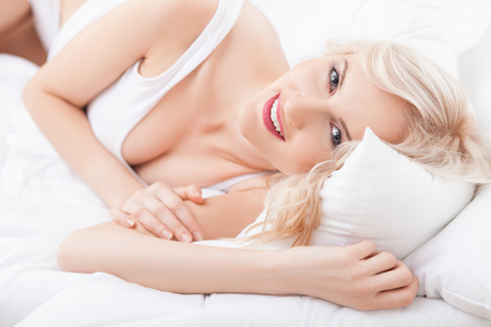 woman pose: Cheerful young woman is lying in bed and smiling. She is looking forward with happiness