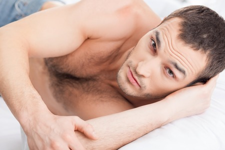 sexualidad: Portrait of attractive man expressing his sexuality. He is lying in bed and looking at camera with passion