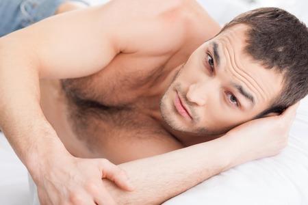 sexualidad: Retrato de hombre atractivo expresar su sexualidad. Que se ha quedado en la cama y mirando a la c�mara con pasi�n Foto de archivo