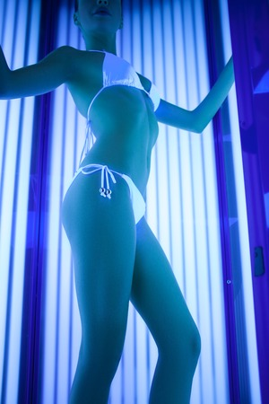 solarium: Pretty girl is standing in solarium with joy. She is posing in white bikini Stock Photo