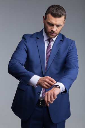 seriousness skill: Waist up portrait of handsome businessman is preparing for meeting. He is standing and adjusting a sleeve of his suit with concentration. Isolated Stock Photo