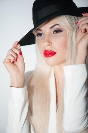 sexualidad: Cintura para arriba retrato de mujer joven y atractiva evidenciando su sexualidad. Ella est� de pie y tocar su sombrero negro moderno. Foto de archivo