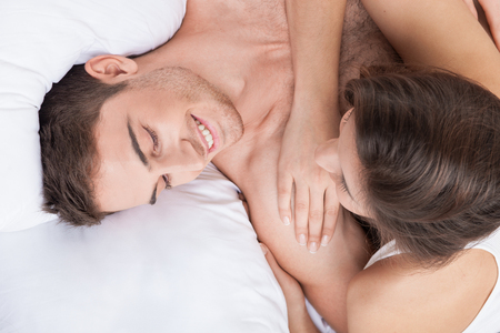 enamorados en la cama: Beautiful young lovers are resting in bed together. They are embracing and talking. The man and woman are smiling