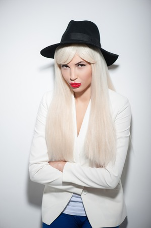 resentment: Attractive young woman is standing in wig and black hat. She is looking at camera with resentment and crossed arms. Isolated